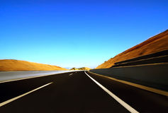 Highway to nowhere. With blue sky and orange embankment on both sides Royalty Free Stock Photography