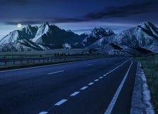 Highway to the tatra mountain ridge. Travel destination concept image. Composite landscape of High Tatra mountain ridge at night in full moon light. Straight stock photo