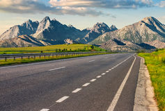 Highway to the tatra mountain ridge. Travel destination concept image. Composite landscape of High Tatra mountain ridge. Straight asphalt highway through green Stock Photography