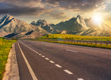 Highway to the tatra mountain ridge. Travel destination concept image. Composite landscape of High Tatra mountain ridge at sunset. Straight asphalt highway Royalty Free Stock Photos