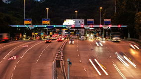 Highway Toll Booth. Zoom Out Shot. City Rush Hour. Cars line up on multiple lanes highway to the toll booths