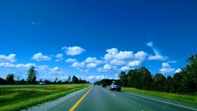 Highway traffic beautiful driving clouds distance. The long road an image taken while I was in the passenger seat of a beautiful day on the road Stock Image