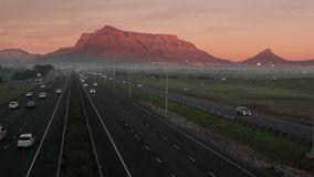 Highway traffic in Cape Town, with Table Mountain in the background, early in the morning. stock video footage