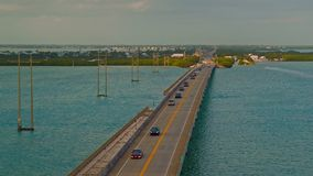 Highway traffic driving on a bridge crossing the ocean stock footage