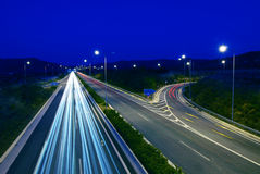 Highway traffic at night. Shot of european motorway taken at twilight - long exposure creates dramatic light trails Royalty Free Stock Image