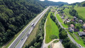 Highway traffic road near a village. Aerial shoot of a highway traffic road with cars and trucks near a village with motorway road for transportation stock video footage