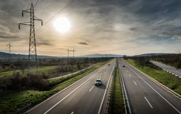 Highway Traffic on a straight road at sunset. Through pastoral landscape Stock Images