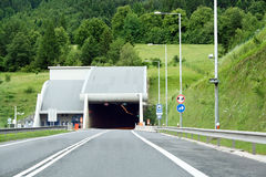 A highway tunnel cutting through a mountain Royalty Free Stock Images