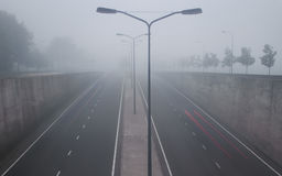 Highway tunnel on misty morning with light trails on the marked road Royalty Free Stock Image