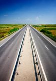 Highway under blue sky. Vibrant landscape with a highway under blue sky Stock Photos
