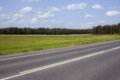 A highway under blue sky with clouds of white Royalty Free Stock Image
