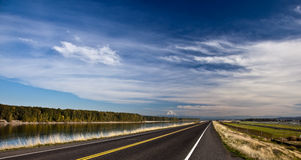 Highway under cloudscape. Scenic view of highway receding under blue sky and cloudscape past Columbia riverbank, Oregon, U.S.A Royalty Free Stock Images