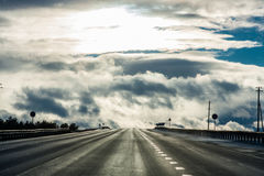 Highway under the dramatic cloudy and sunny sky in stormy weather. In high contrast Stock Photography