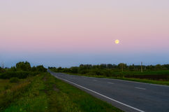 Highway under a full moon. Highway under a full moon, and the sky with the reflection of sunset Stock Photography