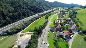 Highway in a valley. Aerial shoot of a highway road with a lot of traffic and small motorway by the highway stock footage