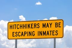 Highway warning sign about hitchhikers that might be escaping in. Mates stock images