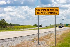 Highway warning sign about hitchhikers that might be escaping in. Mates stock photography