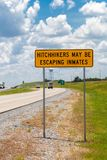 Highway warning sign about hitchhikers that might escaping inmates.  royalty free stock photos