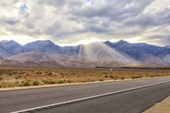 Highway 396, way to  Mammoth lakes area, USA. View from the Highway 395 to mountains and clouds, with sun rays passing through just before sunset Stock Image