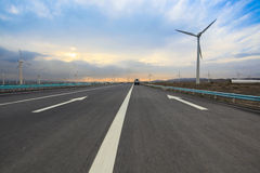 Highway with wind turbines. Generating electricity in sinkiang Royalty Free Stock Image