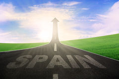 Highway with word of Spain and arrow upward. Picture of empty highway with word of Spain and arrow upward at the end of a road Stock Photo