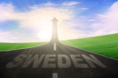 Highway with word of Sweden and arrow upward. Image of empty highway shaped upward arrow with a word of Sweden at sunrise Stock Photography