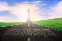 Highway with word of United Arab Emirates. Empty highway shaped upward arrow with a word of United Arab Emirates at sunrise Royalty Free Stock Photo