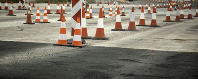 Highway with works cones. Dangerous traffic, construction and symbol, road, street, sign, orange, zone, safety, maintenance, white, warning, city, urban royalty free stock images