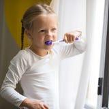 higiena jamy ustnej Szczęśliwa mała dziewczynka szczotkuje jej zęby Obrazy Stock