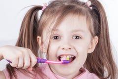 higiena jamy ustnej Szczęśliwa mała dziewczynka szczotkuje jej zęby odosobniony Fotografia Stock
