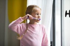 higiena jamy ustnej Szczęśliwa mała dziewczynka szczotkuje jej zęby salowych Obraz Stock