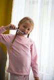higiena jamy ustnej Szczęśliwa mała dziewczynka szczotkuje jej zęby zbliża okno Fotografia Royalty Free