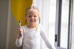 higiena jamy ustnej Urocza mała uśmiech dziewczyna szczotkuje jej zęby Zdjęcia Stock
