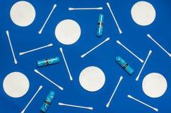 Higiena produkty: round biali bawełniani ochraniacze i bawełniani mopy są na barwionym tle fotografia royalty free
