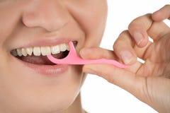Higiene de la cavidad bucal La chica joven limpia los dientes con seda, imagenes de archivo