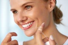 Higiene dental Mulher bonita que Flossing os dentes brancos saudáveis fotos de stock