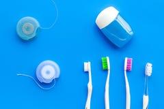 Higiene oral diária para a família Escova de dentes e fio dental na opinião superior do fundo azul fotografia de stock