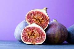 Higo maduro orgánico aún de la vida colorida en fondo violeta púrpura hermoso Foco selectivo en medios ficus cortados de la fruta Imagen de archivo