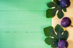 Higos frescos con las hojas en fondo de madera verde Foto de archivo