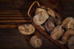 Higos secados en una pequeña cesta en fondo de madera Fotos de archivo