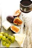 Higos, uva, queso y vidrio de vino Imagen de archivo