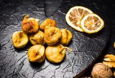 Higos y rebanadas secados del limón en una placa oscura Imagenes de archivo