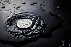 Higth speed water. Coin of the queen splashing on water at fast speed photography Royalty Free Stock Image