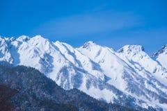 Hij bergen van de winter van Japan torenhoog in blauwe hemel Royalty-vrije Stock Afbeeldingen