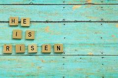 Hij is Toegenomen Christelijke blokken op een blauwe houten plankachtergrond Royalty-vrije Stock Foto