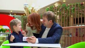 Hij vader met de video van het zoonshorloge op telefoon De moeder benadert de familie van een rug Jonge gelukkige familie bij bin stock videobeelden