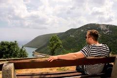 Hij zitting op het houten bank letten op op het overzees en mooi s Royalty-vrije Stock Foto's