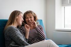 Hija adolescente con la madre que come el chocolate Foto de archivo libre de regalías