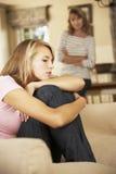 Hija adolescente gruñona que se sienta en Sofa With Mother In Background Imagenes de archivo