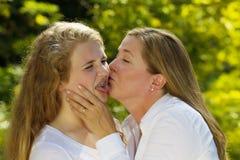Hija adolescente no feliz de su madre que la besa Imagen de archivo libre de regalías